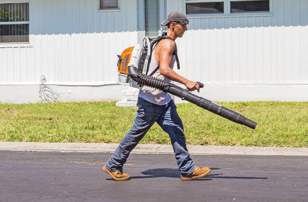 man walking with leaf blower