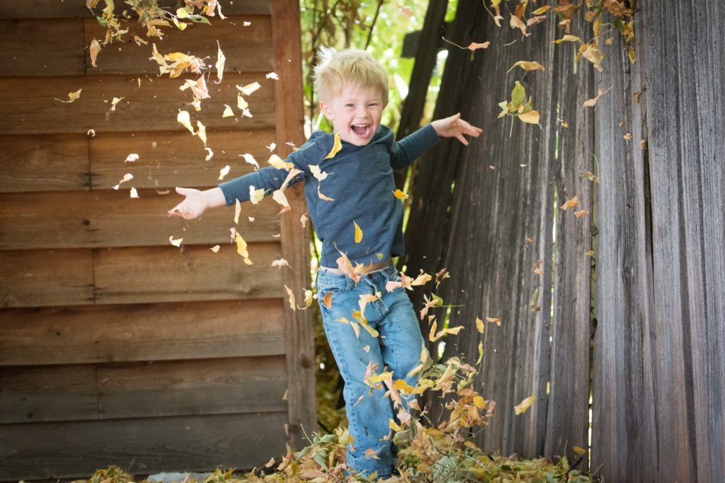 boy jumping in pile of leaves